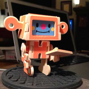 Little paper robot holding out a note